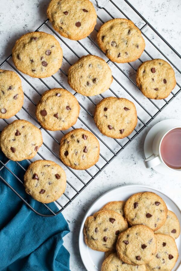 gluten free chocolate chip cookies on a baking sheet and on a plate with a cup of tea
