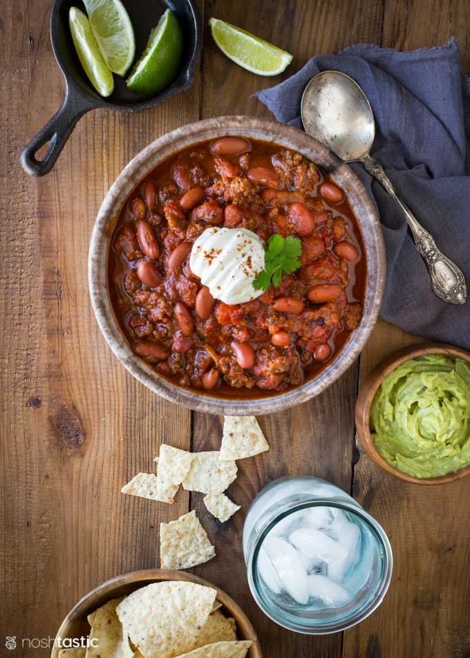 Instant pot chili in a bowl with guacamole and glass of water on the side