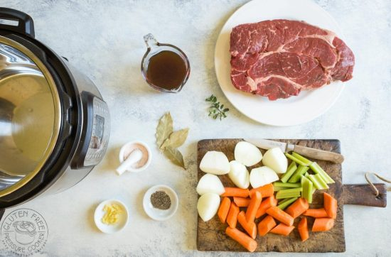 Ingredients required to make a pressure cooker pot roast, beef, carrots, potatoes, celery and herbs.