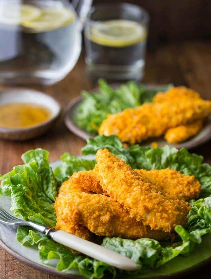 gluten free chicken tenders on a plate with glass of water