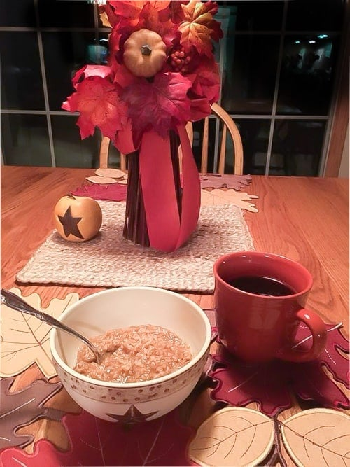 pumpkin oatmeal on a table with Fall decorations and a cup of coffee