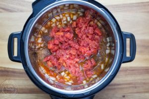 pot roast, taco spices and tomatoes in a pressure cooker