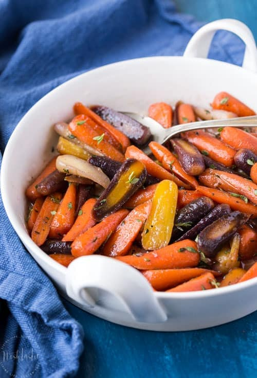 Quick and easy Paleo glazed carrots made with honey, olive oil and fresh thyme.You can cook them on the stovetop or bake them in the oven! #paleo #paleorecipe #glutenfree #paleocarrots #paleosides #paleoholidays #paleothanksgiving