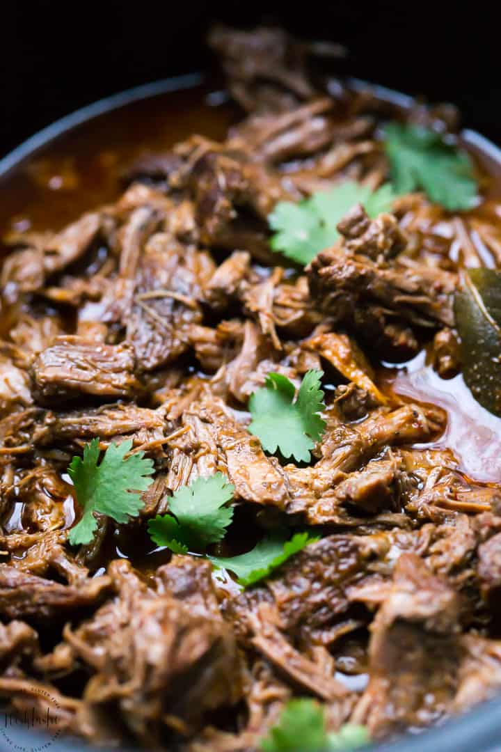 barbacoa beef in a slow cooker with cilantro leaves