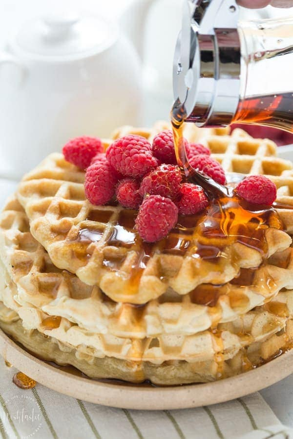 Plate of Gluten Free Waffles with raspberries and maple syrup poured over the top.