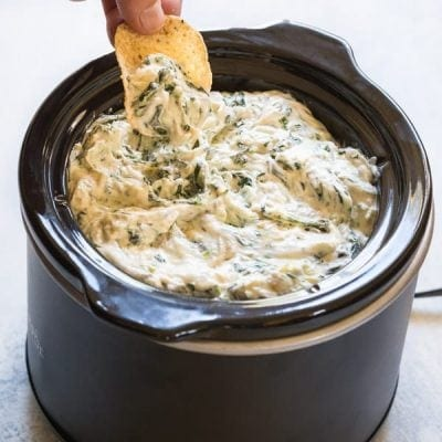 spinach and artichoke dip recipe in your crockpot or slow cooker! Made with cheese, spinach and artichoke hearts #spinachartichokedip #gameday #gamedayrecipes #chipsanddip #cheesedip #crockpotdip #partyfood #appetizer #noshtastic #glutenfree #glutenfreeappetizer
