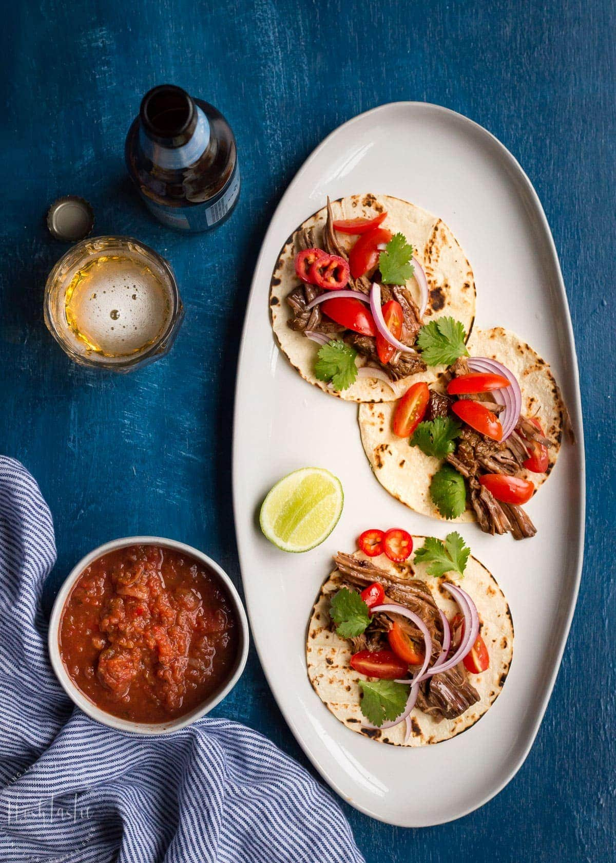 Salsa, cider and three beef tacos on a plate