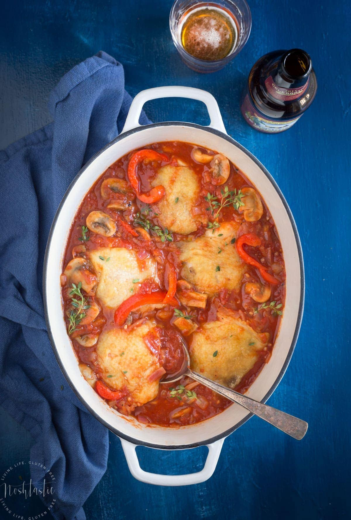 Overhead view of dutch oven with chicken cacciatore and a glass of beer to the side