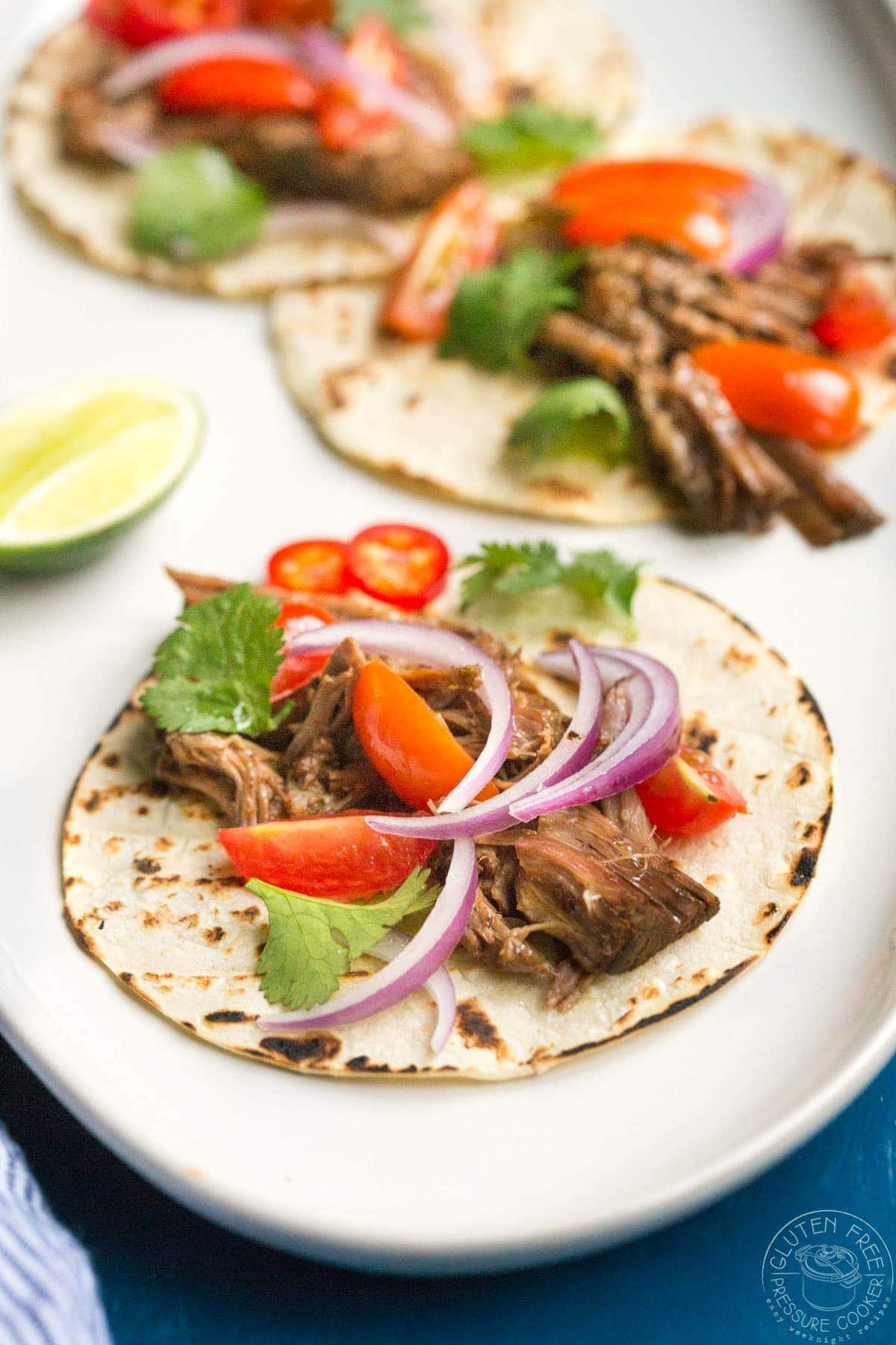Barbacoa tacos with red onions and tomato on top