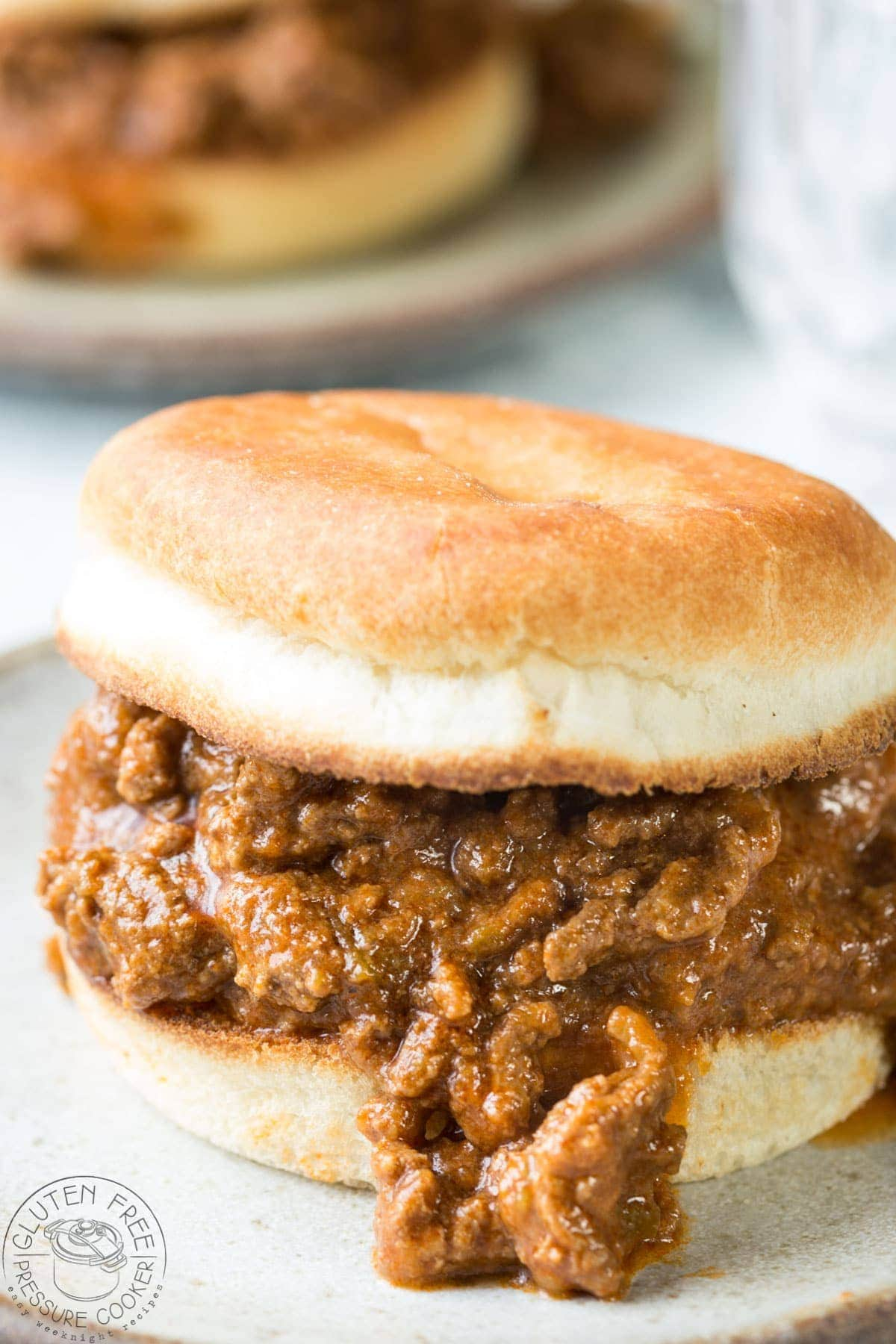 Instant Pot Sloppy Joes recipe on a plate with bread roll