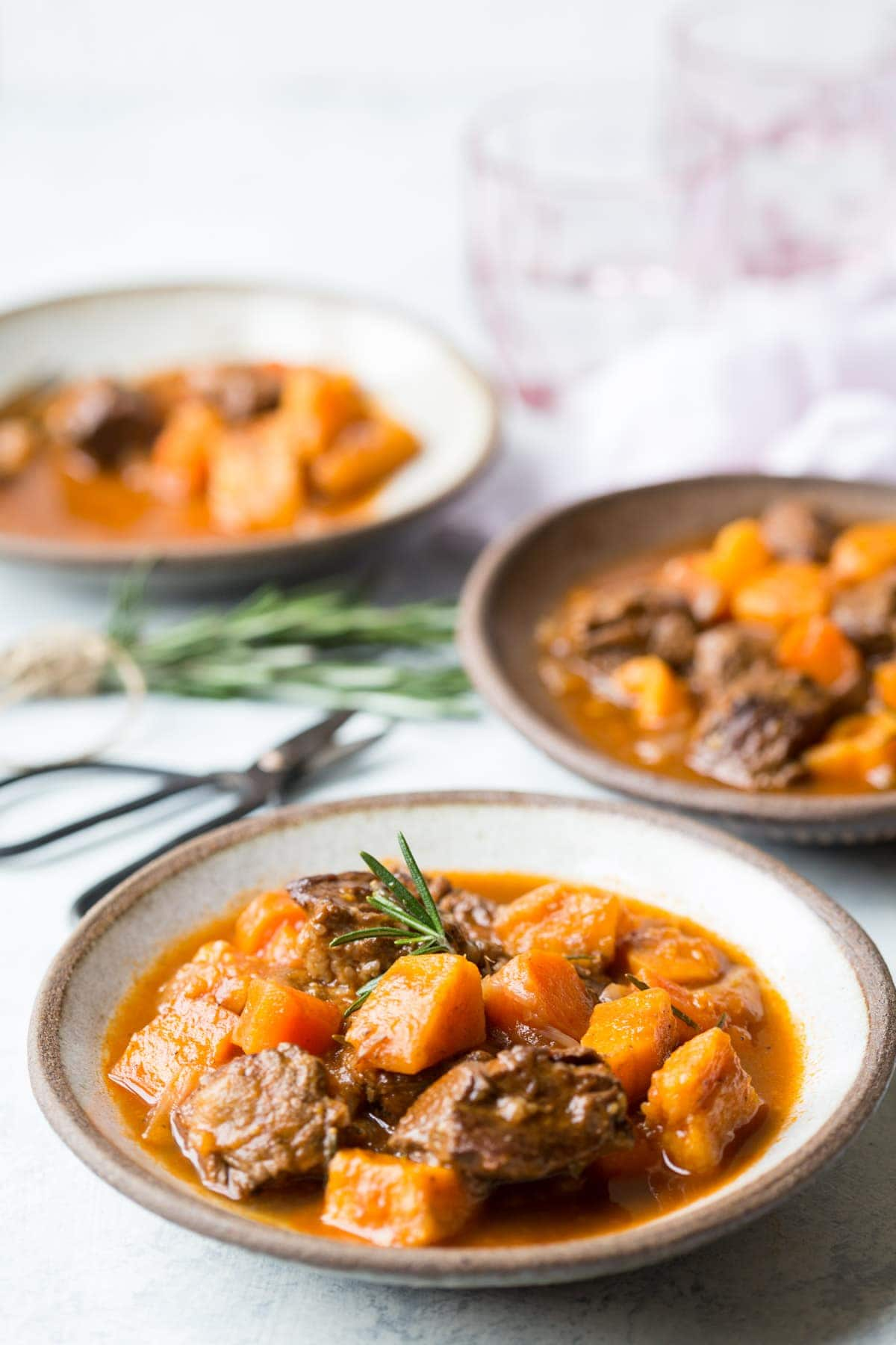 beef and sweet potato stew in a bowl with rosemary