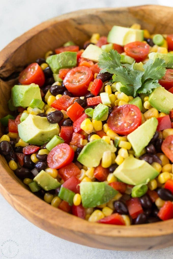 avocado corn salad with tomatoes in a bowl