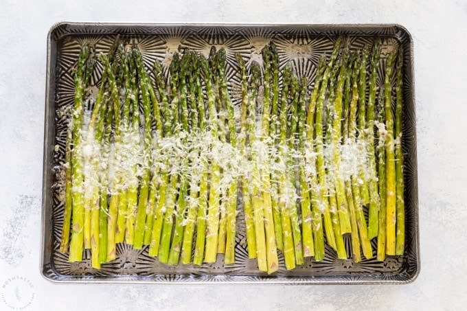 asparagus on a sheet pan with parmesan cheese