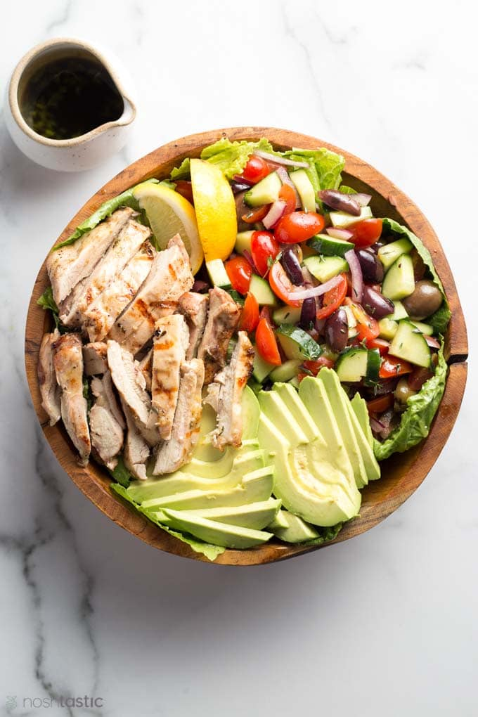 chicken salad in a bowl with dressing on the side