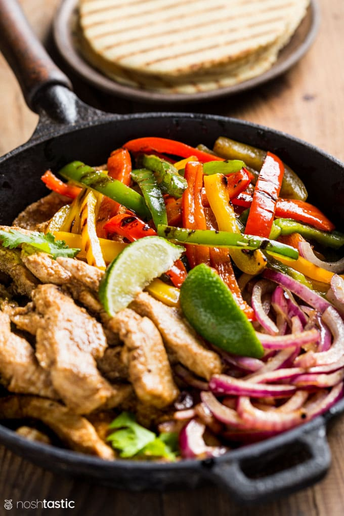 Low Carb Chicken Fajitas in a skillet with limes