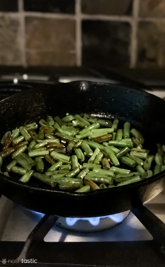 charred green beans in a skillet