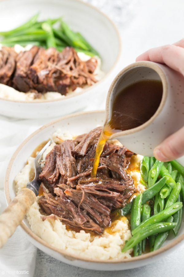 Pot roast in a bowl with green beans and gravy