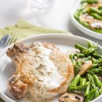Cooked pork chop on a plate with asparagus and mushrooms