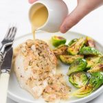 Chicken breast on a plate with lemon sauce pouring over the top