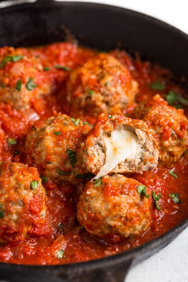 Mozzarella meatballs in a cast iron skillet with marinara sauce