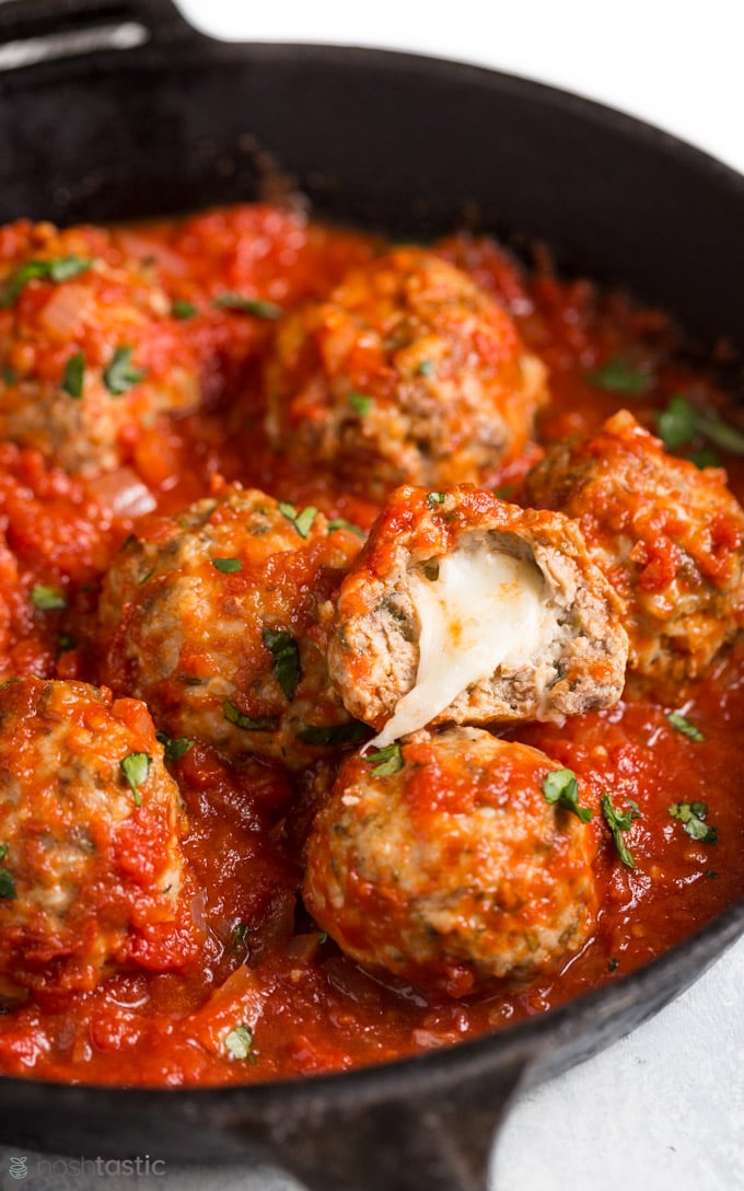 Mozzarella meatballs in a cast iron skillet with marinara sauce