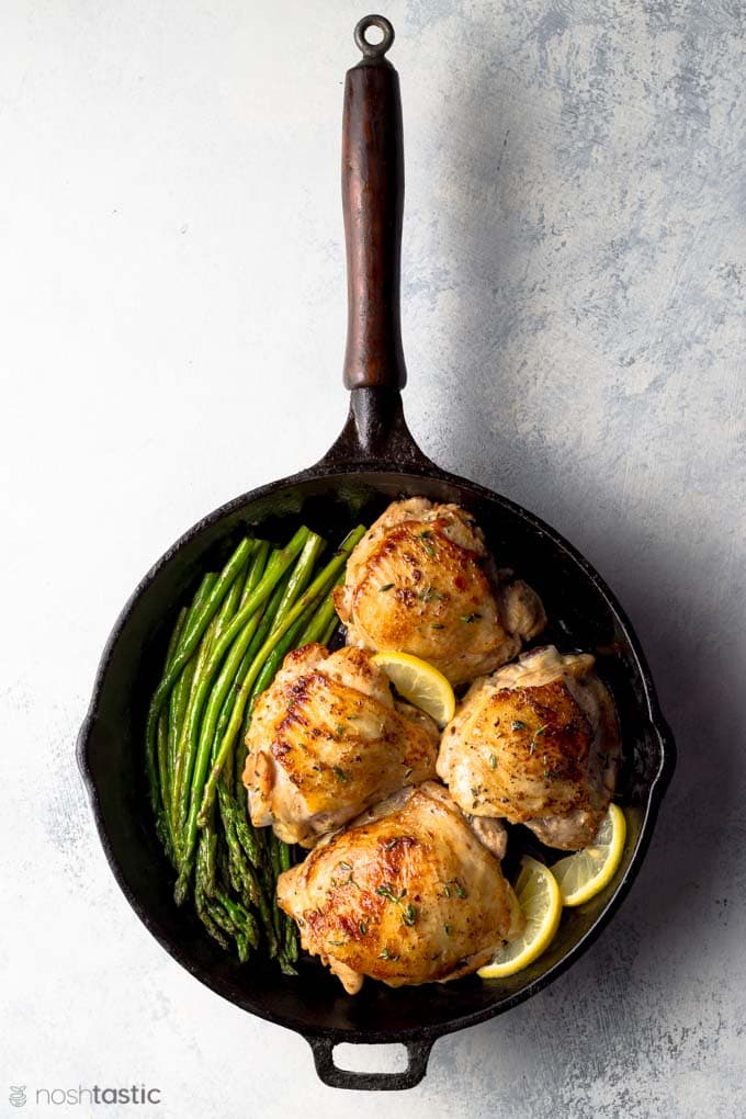 Pan cooked lemon thyme chicken thighs with asparagus and lemon slices