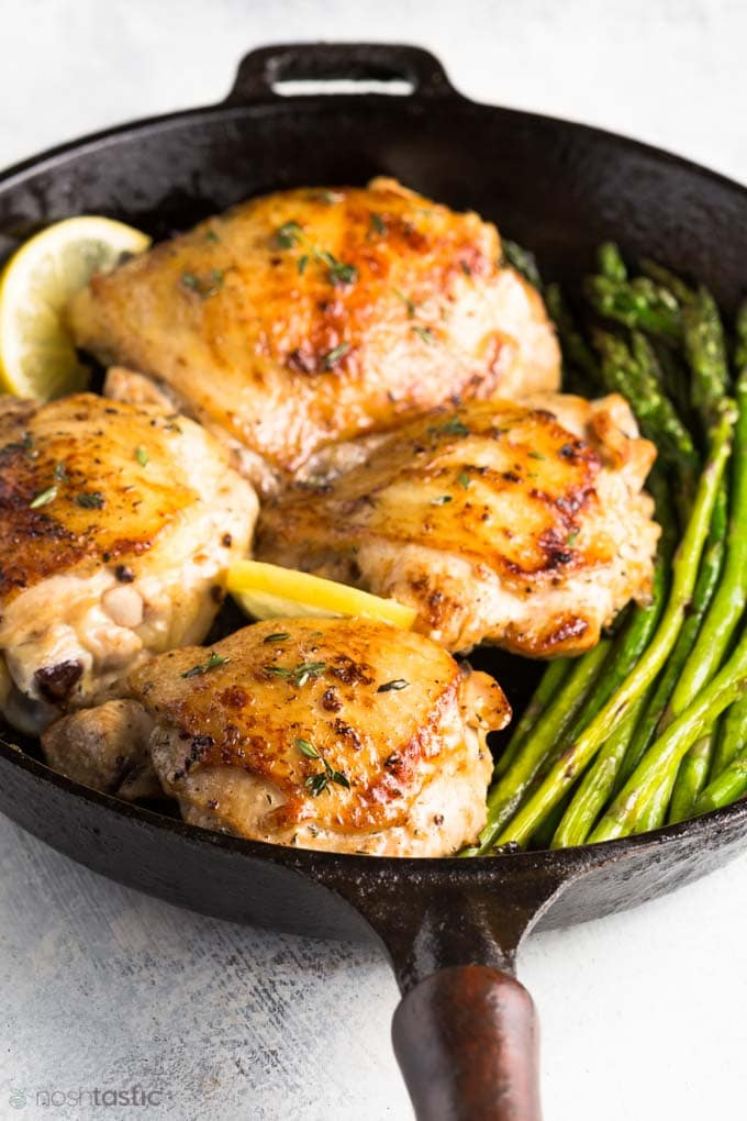 Roasted Lemon Thyme Chicken with asparagus in a cast iron skillet.