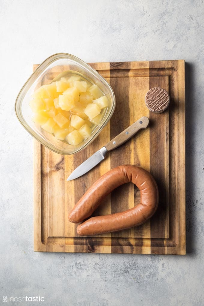 Ingredients for sausage pineapple bites on a board