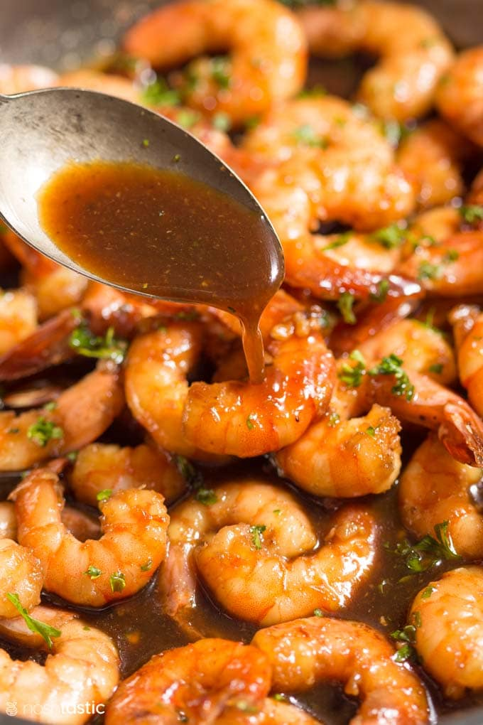 spooning honey garlic sauce over cooked shrimp