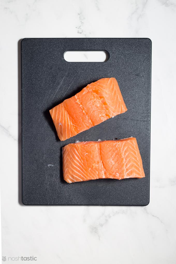 Two salmon fillets on a cutting board
