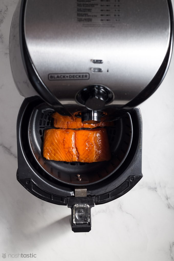 Salmon in the drawer of an air fryer waiting to be cooked