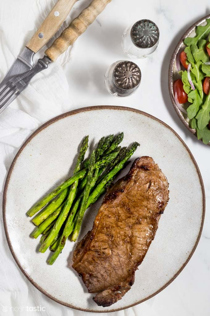 Air fried steak on a plate with asparagus