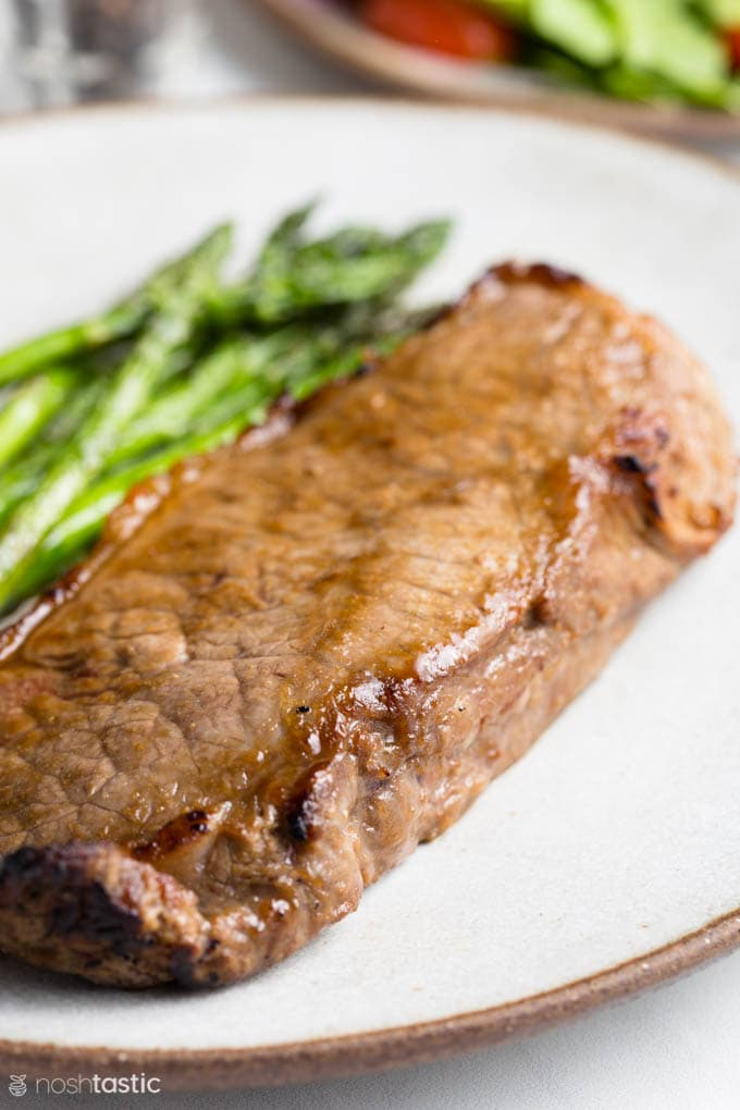 cooked strip steak on a plate with asparagus