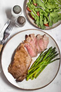 Sliced steak on a plate with asparagus and side salad