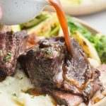 Instant pot short ribs on a plate with gravy poured over