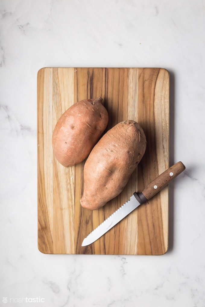 two sweet potatoes on a board with a knife