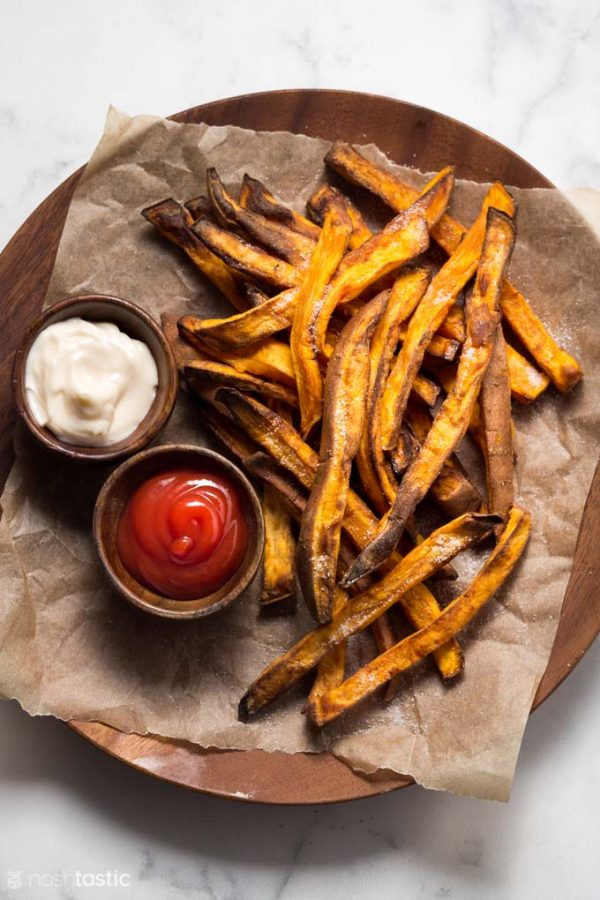 sweet potato fries on a plate with ketchup and mayo