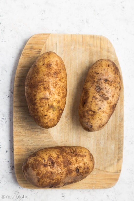 Washed Russet potatoes on a wood board