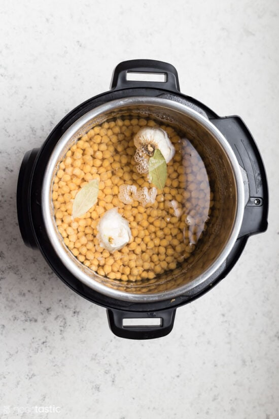 uncooked chick peas, bay leaves and garlic in a pressure cooker