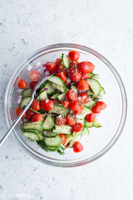 cucumber and tomato in a bowl with herbs