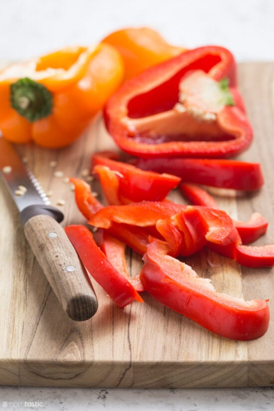 sliced red bell peppers on wooden board with knife