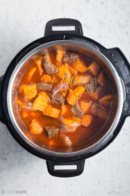 cooked beef stew inside a pressure cooker