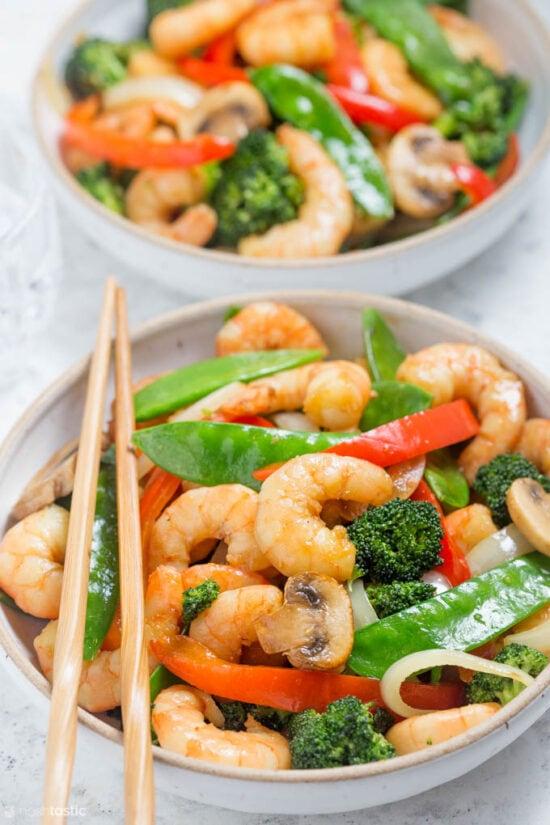 shrimp broccoli snow peas stir fry in bowl with chopsticks