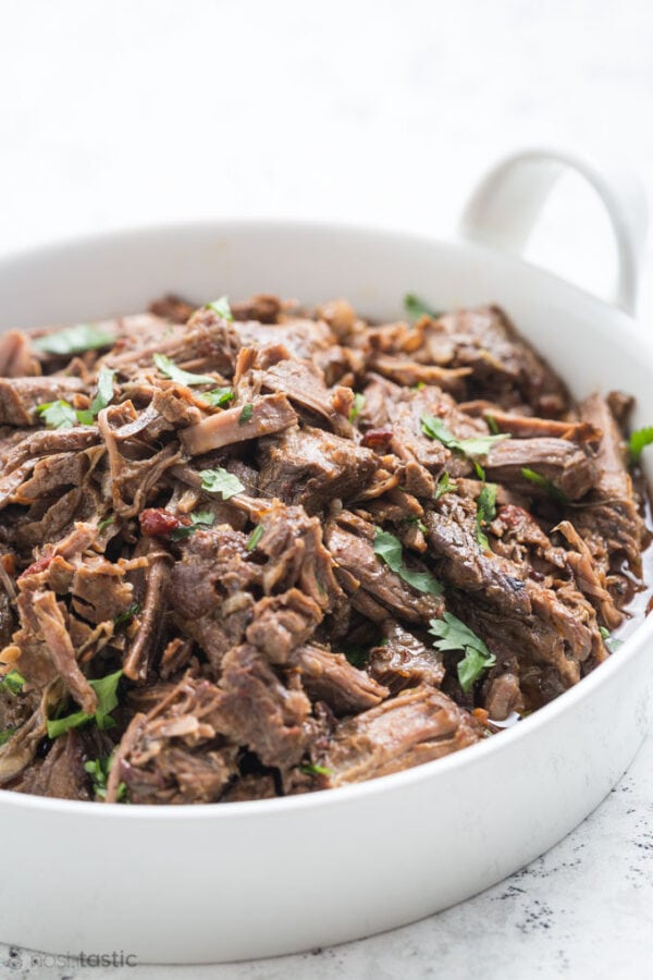 Shredded barbacoa beef in a white dish