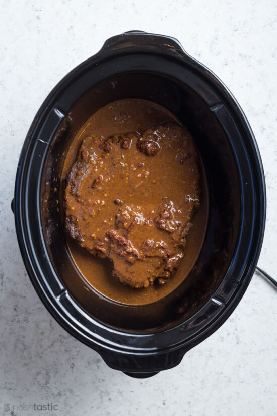 chuck roast covered with Adobo sauce in a slow cooker