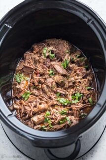 barbacoa beef in a slow cooker with cilantro garnish