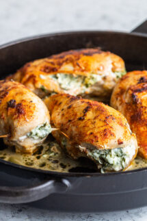 chicken stuffed with spinach in a skillet