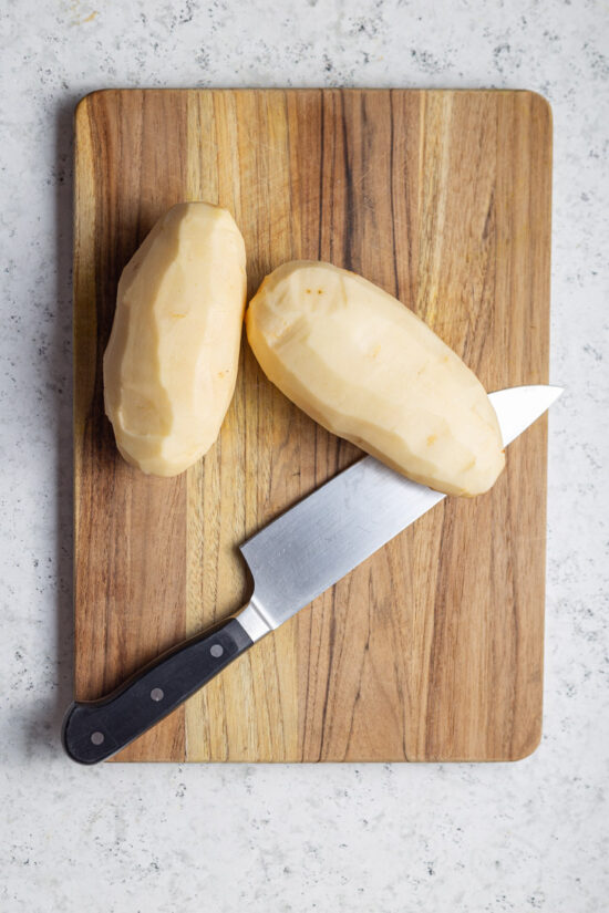 two potatoes and knife on board